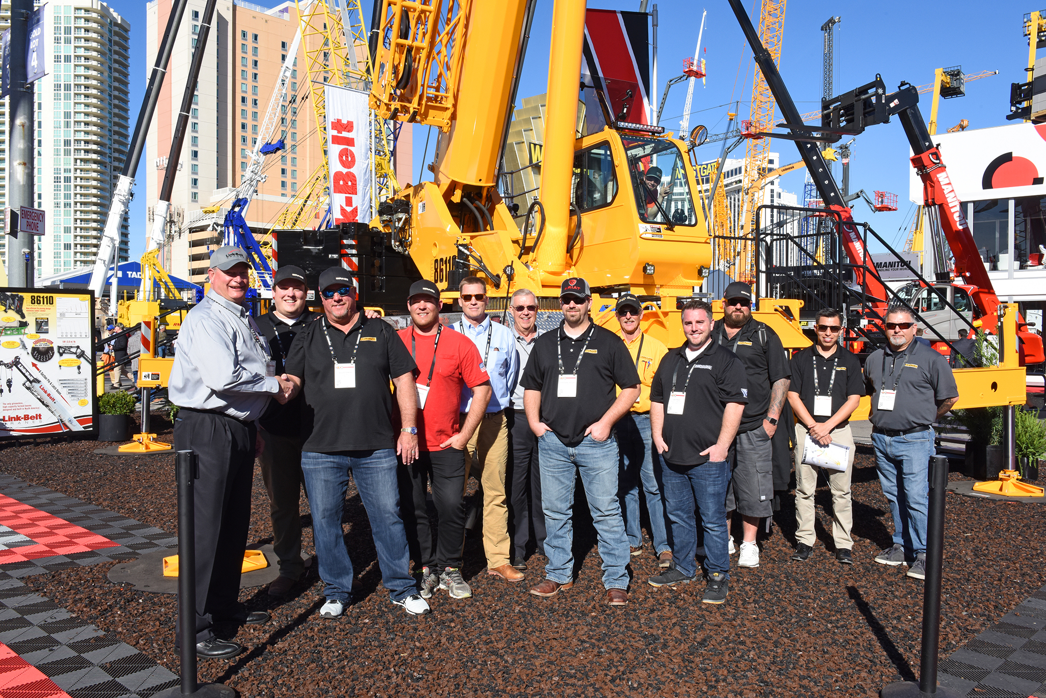 Bragg Crane Service representatives take possession of a new Bragg custom color Link-Belt HTC-86110 at CONEXPO-CON-AGG 2017 as part of their eight crane purchase.